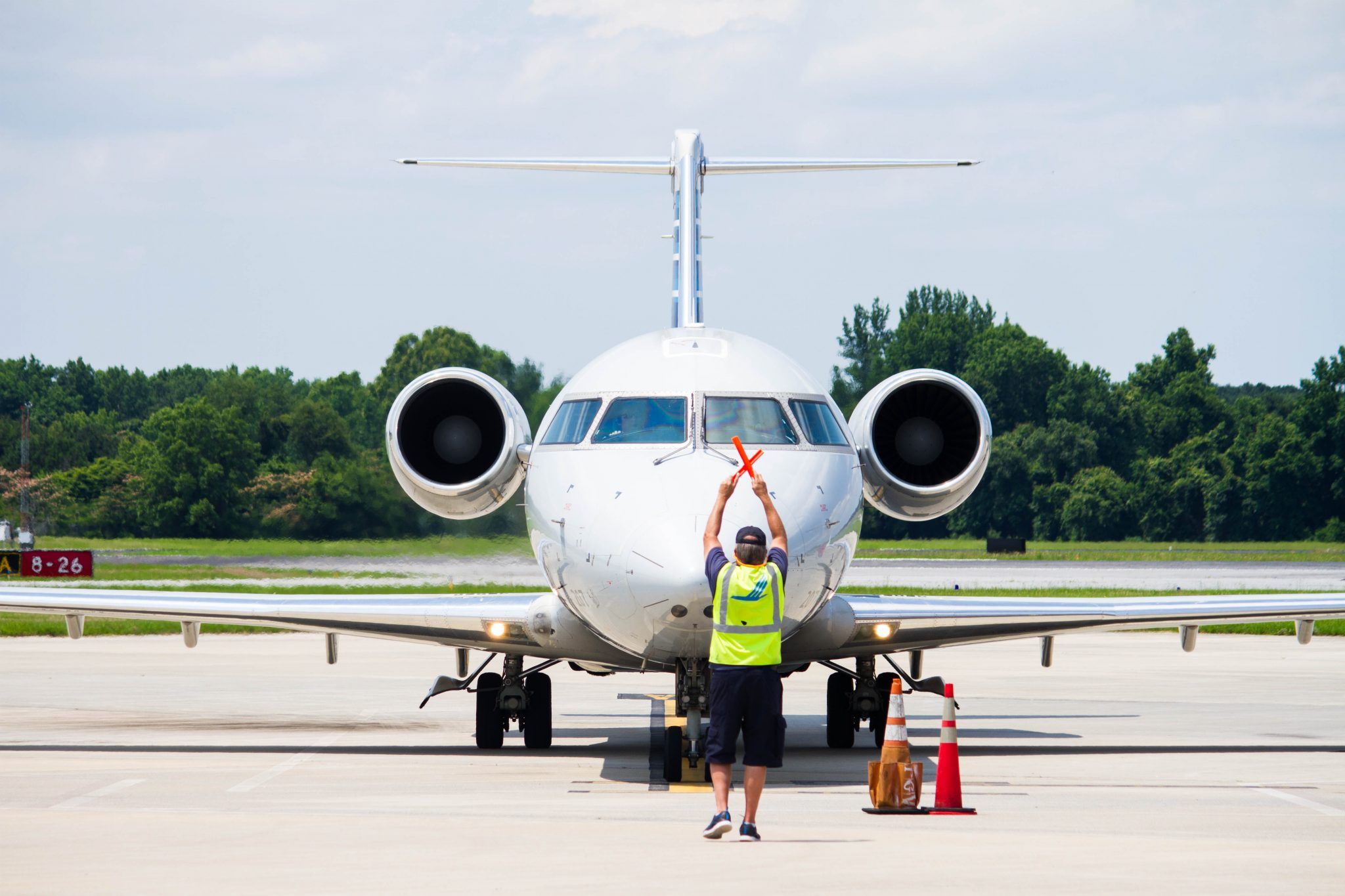 Plane on runway with marshaller